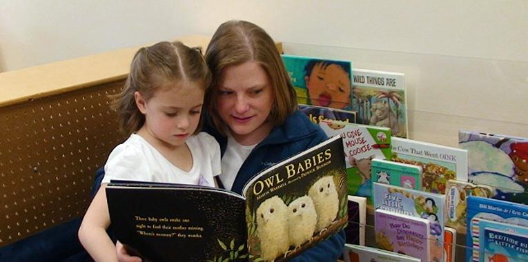 Brandy Minikey, Parent Liaison for the Great Start Collaborative in Montcalm County, reads a book to a young student.